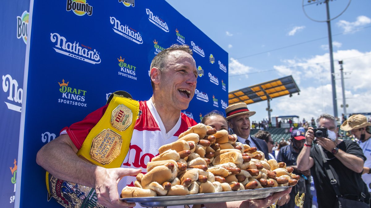 Winners Joey Chestnut and Michelle Lesco, obscured behind hot dogs, pose at the Nathan's Famous...