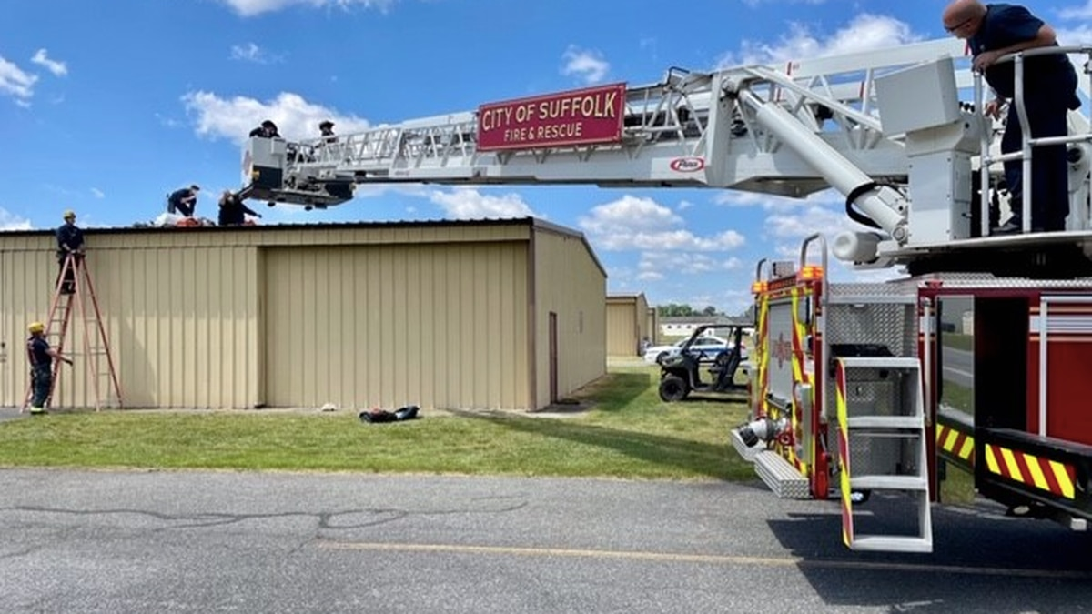 Suffolk's fire and rescue team uses a ladder truck to assist a skydiver who landed on an...
