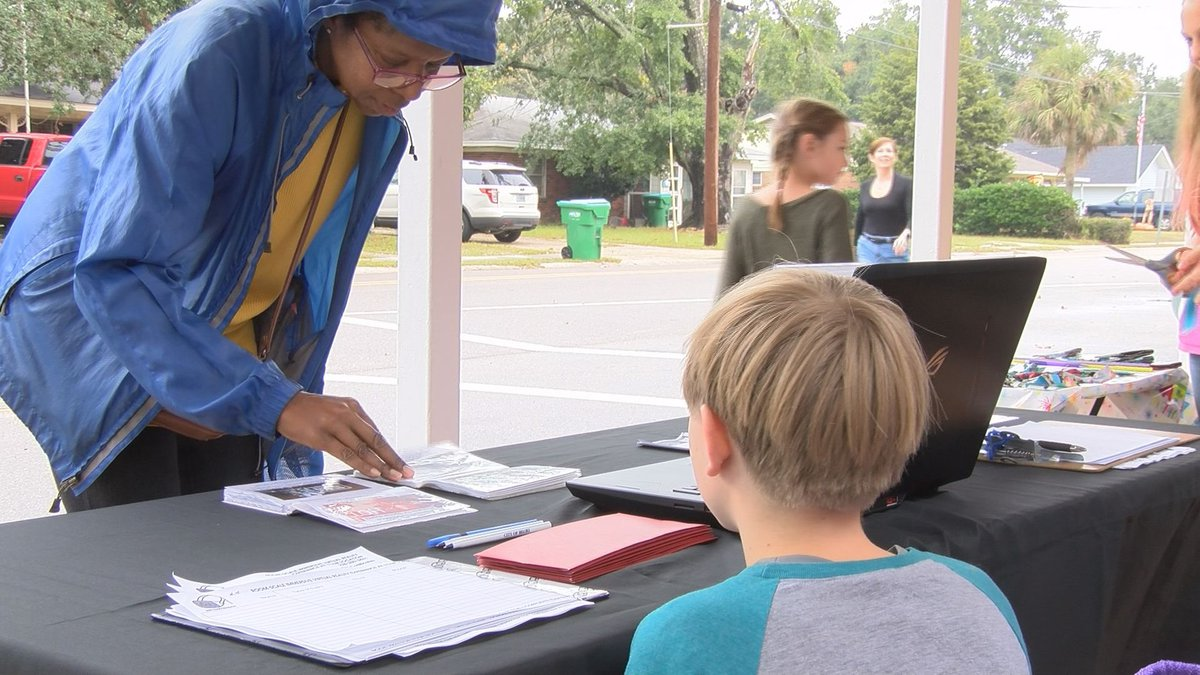 A woman looks at a young boy's inventory at the children's business fair.