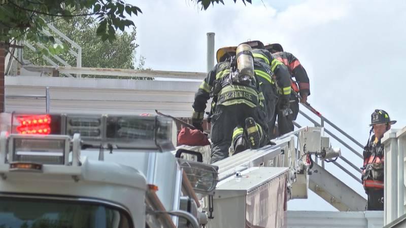 Richmond firefighters climb ladder truck.