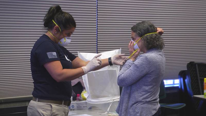 A woman is fitted for an N95 mask.