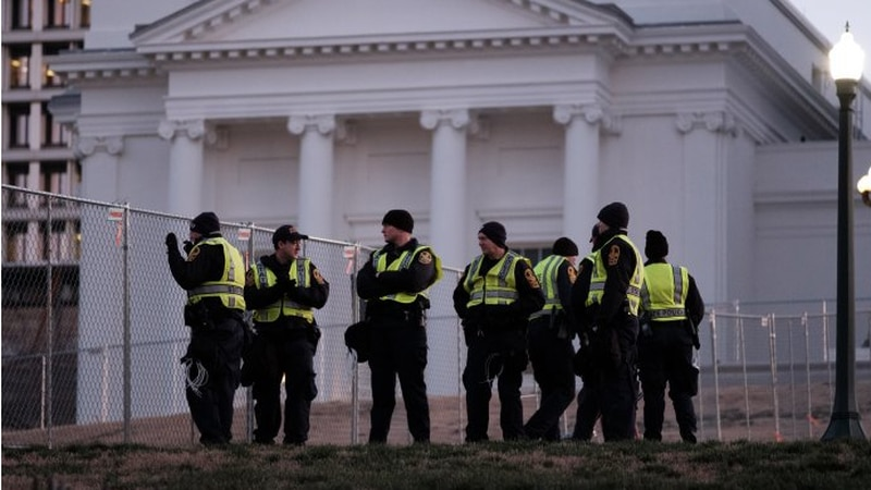 Police on Capitol Square at dawn stand alongside fencing set up to corral attendees of a large...